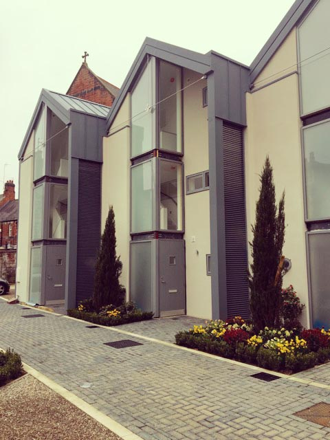 Carter Grice Project - Modern exterior facade with yellow flower borders and large glass windows in new Harrogate city development