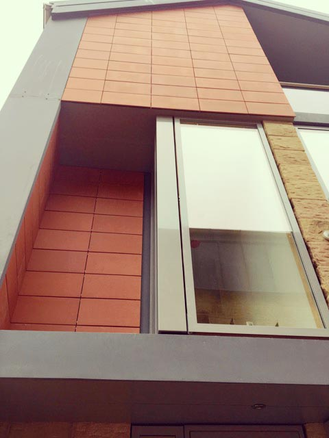 Carter Grice Project - Modern exterior worms eye view looking up orange panelled facade of new Harrogate city development