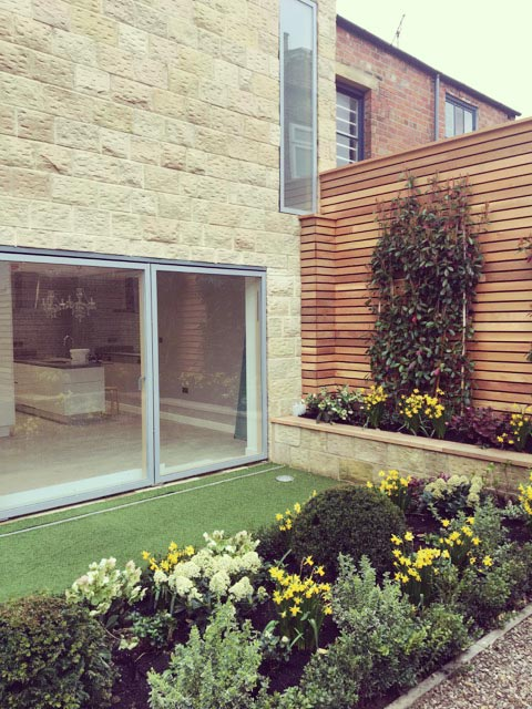 Carter Grice Project - Modern, small garden with astro turf grass and yellow flower borders in new Harrogate city development